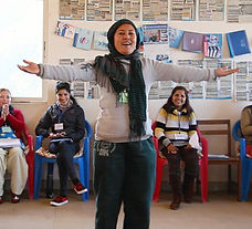 Nepali woman singing in front of a group of women who are smiling at her