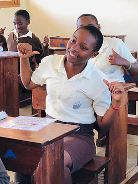 """Uganda student smiling with thumbs point at herself with orange colored overlay and """"Uganda"""" written in the center"""