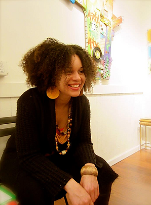 Smiling Afrolatinx woman with circle earrings and artwork behind her
