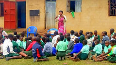 Ugandan school teacher standing in front of a group of students who are sitting on the ground, as she enthusiastically teaches them about how to heal from trauma