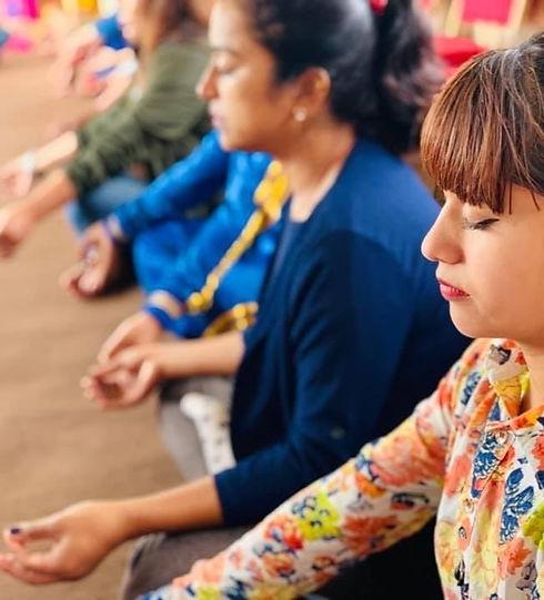 Nepali women sitting with eyes closed in meditation
