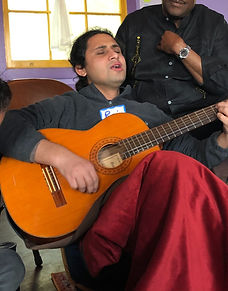 Nepali man playing the guitar and singing with eyes closed while a Black man sits behind him, looking on
