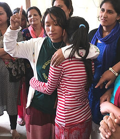 Young Nepali women hugging emotionally while other women around them look on
