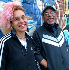 Black woman with pink hair and elder Black man wearing a cap standing in front of a graffiti wall smiling