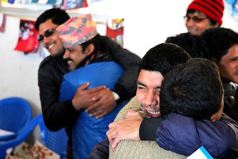 Group of Nepali men hugging and smiling