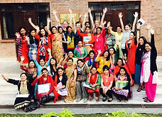 Nepali women posing for a group photo wearing colorful tunics with hands up in the air in a joyful pose