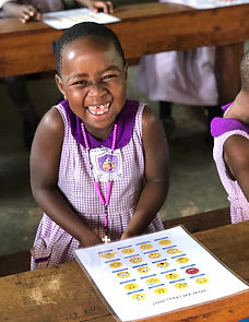 Ugandan preschool child smiling with an emotions chart in front of her