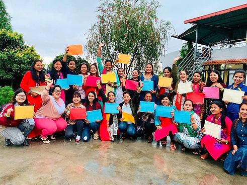 Nepali women smiling for a group photo, wearing colorful tunics and holding certificates in their hands after completing a trauma healing workshop