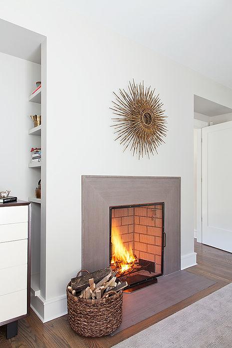 Limestone fireplace, vintage starburst mirror, hidden bookshelf niche