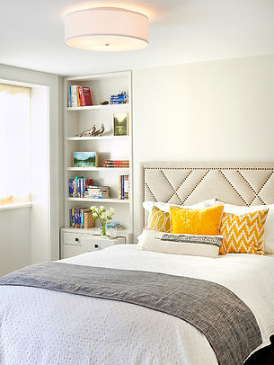 Neutral guestroom with yellow pillows, nailhead headboard