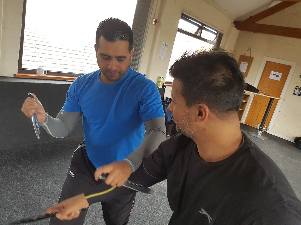 Sr Instructor Kam Dhiman (right) helping Sunny (left) with his drills