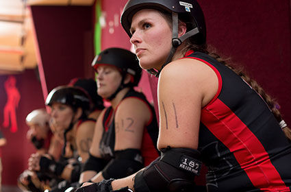 roller girls geared up sitting on bench