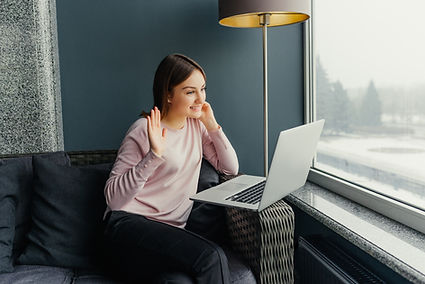 A young woman sitting on the couch and doing online therapy on her laptop