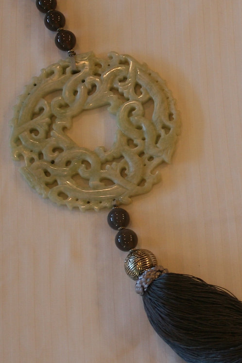 Large celadon carved disc with grey tassel