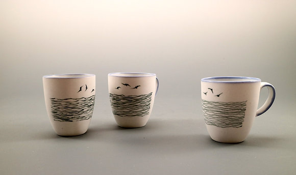 White porcelain cups, black slip decorated. Sold per pair.