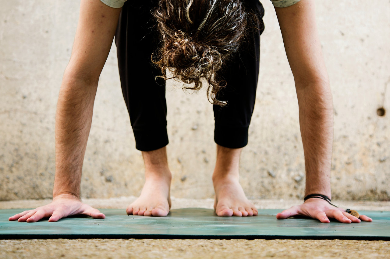 man with bun on yoga mat