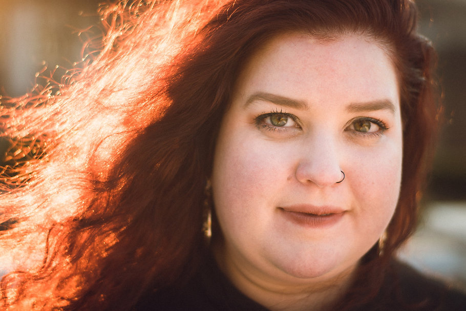 Portrait image of Paulina in which she is slightly smiling and backlit, with vey fiery re hair ad green eyes.