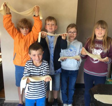 Kids making sheets from fresh dough