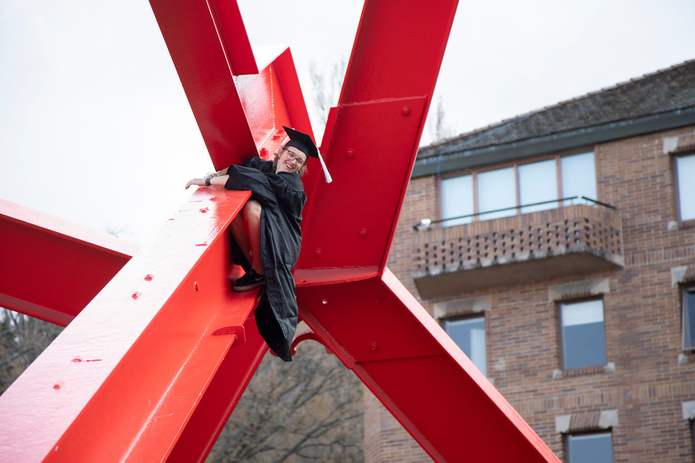 """Riley Marshall climbs the For Handel sculpture after graduating with a B.A. in Elementary Education at Western Washington University on Saturday, Mar. 23, 2019. The 15-foot sculpture, known as """"the Red Mosquito"""" by students, is a popular climbing obstacle despite the university's attempts to discourage the challenge of climbing the 20-foot metal sculpture. (The Western Front)"""