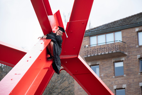 """Riley Marshall climbs the For Handel after graduating with a B.A. in Elementary Education at Western Washington University on Saturday, Mar. 23, 2019. The 15-foot sculpture, known as """"the Red Mosquito"""" by students, is a popular climbing obstacle despite the university's attempts to discourage the challenge of climbing the 20-foot metal sculpture. (The Western Front)"""