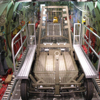 """Part Number: 70-000-1  DESCRIPTION  The unit consists of a steel frame with aluminum steps, platform, and handrails. A drip pan is located in the center and has a valve for draining fluids. The tow-bar can be folded up. The steps can be stored on the cross tube of the mast.  FUNCTION  The unit is used for transportation, storage, maintenance of the Rolls Royce AE2100D3 and the Allison T56-D22, A-9D, 7A, -14 (with adapter), -15, -425 (with adapter),-427 (with adapter).  DIMENSIONS AND WEIGHT  182"""" (L) X 92"""" (W) X 103"""" (H) X 2,976 lbs."""