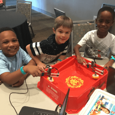 Friends building beyblades lego robots at a birthday party
