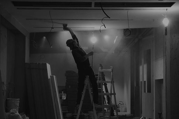 Tradesman working on ladders in a room under construction.jpg
