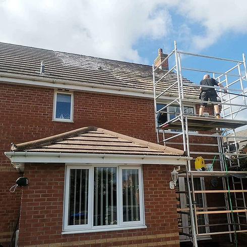 A roof being cleaned on a scaffolding fr