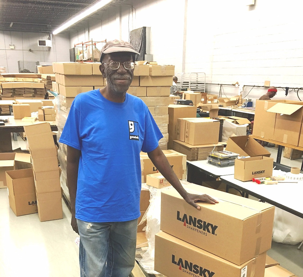 Lester Walker, smiling, stands next to a stack of packaged Lansky Sharpeners in the Goodwill Warehouse