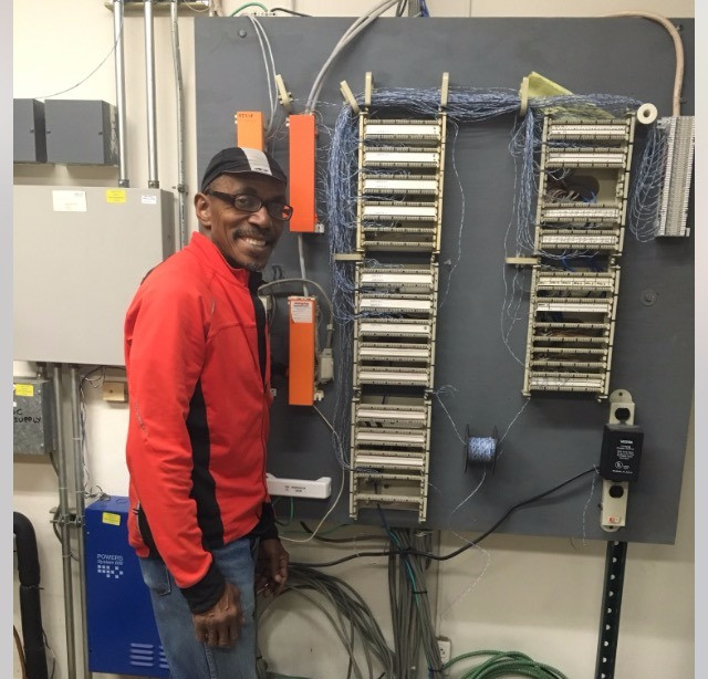 Edward Parker stands next to an electrical wiring panel, smiling