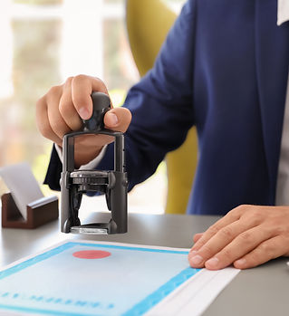 Notary stamping document at desk in offi