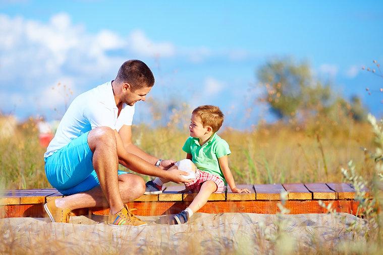 הורה מגיש עזרה ראשונה לילד