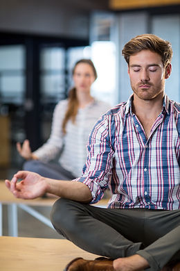 Business people performing yoga on table in office