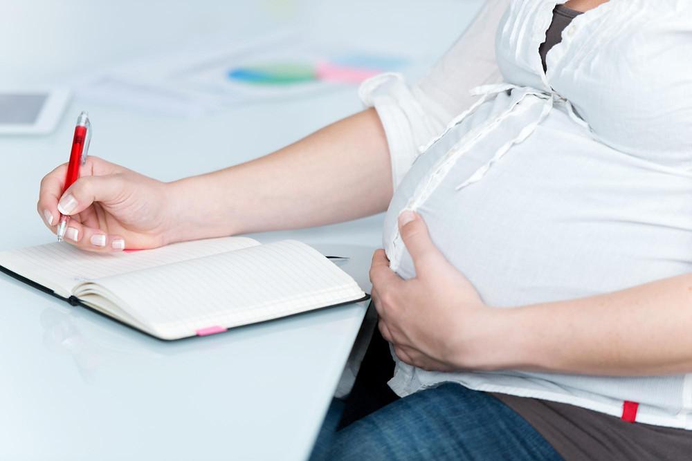 Mulher grávida escreve em um caderno os seus desejos para o parto