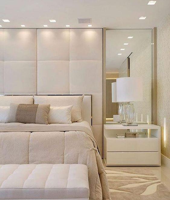 Mesa de cabeceira com espelho amplo complementando a decoração do quarto.