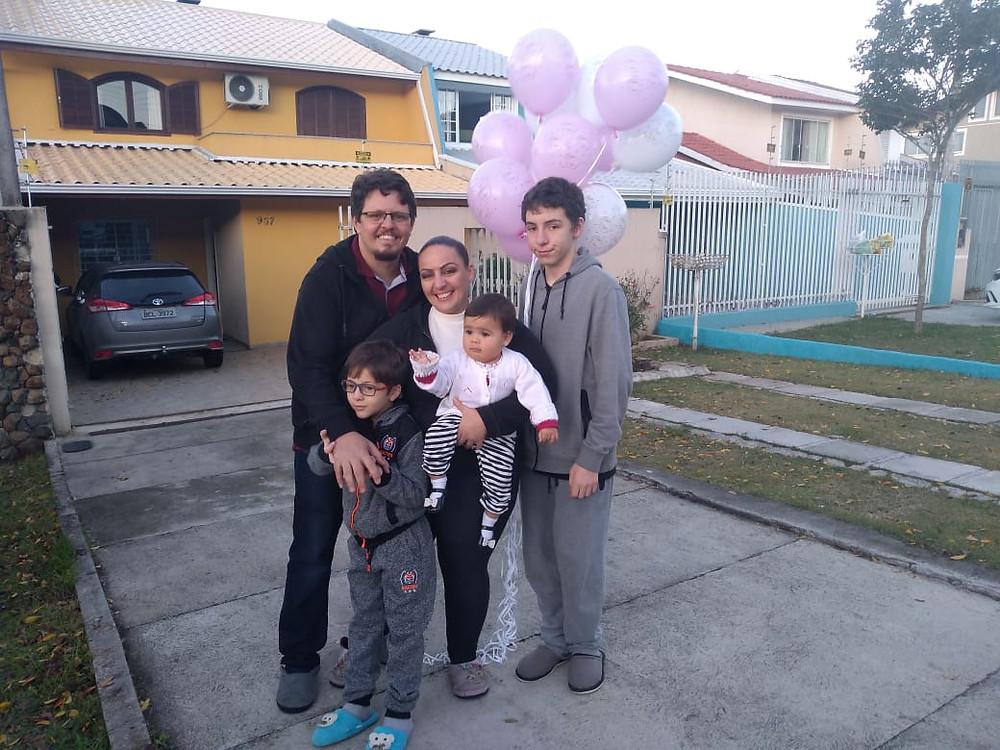 Casal com três filhos em frente de casa segurando balões coloridos