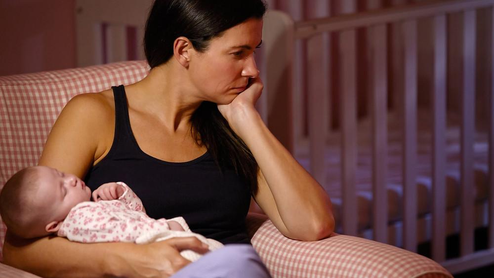 mamãe segurando um bebê sozinha na poltrona demonstra a solidão na maternidade e a  importância das visitas do amigos e da família