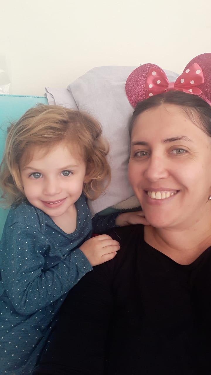 Mãe usando tiara do Mickey com sua filha Ana de dois anos