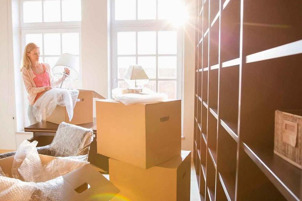 Mulher jovem cercada por caixas de mudança desembalando um abajur próxima a uma estande depois da mudança
