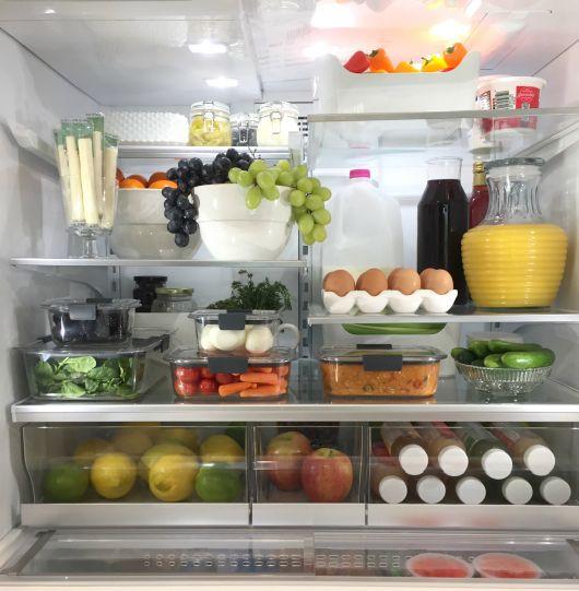 Interior de uma geladeira repleta de alimentos das mais variadas cores e tipos em potes apropriados e bem organizados