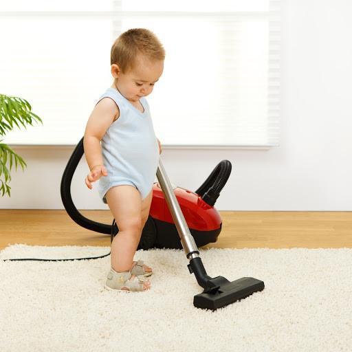 Bebê passando aspirador no tapete