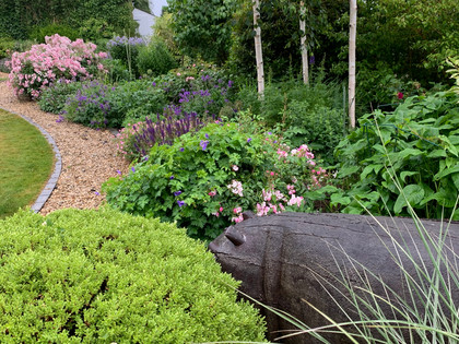 A carved hippo from South Africa half hidden in the planting