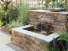 Slate-clad water feature with illuminated letterbox waterfall