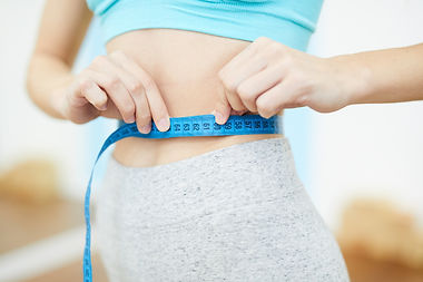 unrecognizable-woman-measuring-waist-in-