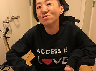 "Asian American woman in a wheelchair wearing a black long-sleeved shirt that says ""Access Is/ LOVE"" with a red heart as the 'O' in LOVE."