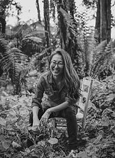 Black and white photo of a Korean woman smiling with long hair and glasses, sitting on a wooden chair with plants and trees all around her.