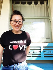 "Korean woman wearing large glasses and hoop earring smiling at the camera with a black t-shirt that says ""ACCESS IS LOVE"" in white. The ""O"" in ""LOVE"" is a red heart. She is sitting on an aqua colored wooden bench in front of a window with white curtains."