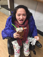 Photo of Asian American woman in a wheelchair smiling up at the camera holding an ice cream in one hand. She is wearing a puffy purple coat, red scarf, and colorful pants.