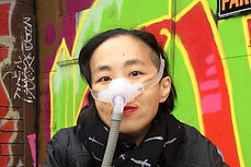 Photo of Asian American woman in a wheelchair. She is wearing a black jacket with a black patterned scarf. She is wearing a mask over her nose with a tube for her Bi-Pap machine. Behind her is a wall full of colorful street art.
