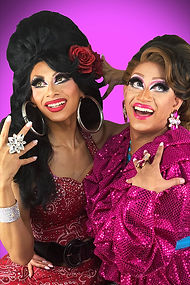 Casavina on the left is wearing black beehive wig, silver hoop earrings, red dress, and red lipstick. Selena on the right is wearing short brown wig, pink lipstick and pink ruffle blouse.